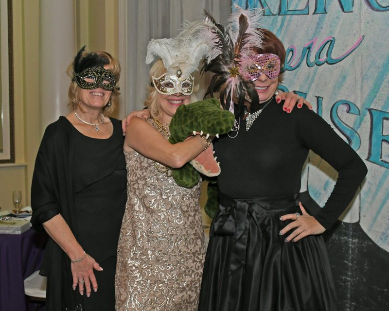 Three woman with mardi gras masks on and a stuffed crocodile at Mardi Gras for AIM Services