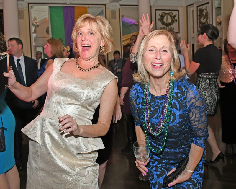 Two woman dancing at Mardi Gras for AIM Services
