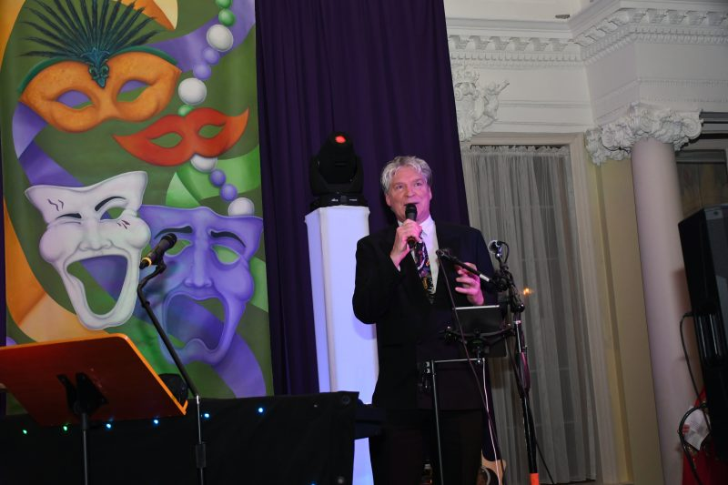 Master of ceremonies Walt Adams speaking to crowd at Mardi Gras for AIM Services