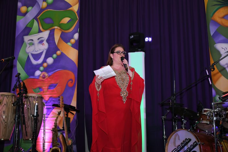 Gala Co-Chair Beth Alexander speaking to crowd at Mardi Gras for AIM Services