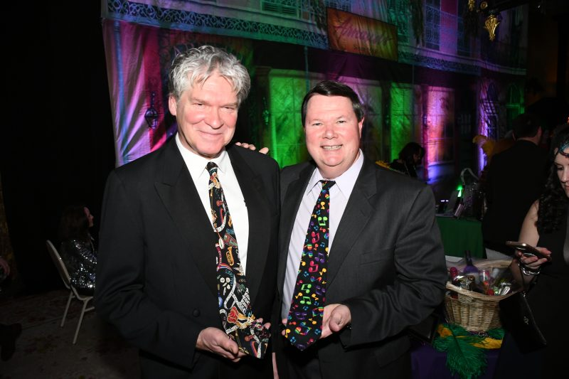Two men with festive Mardi Gras themed ties at Mardi Gras for AIM Services