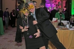 Couple laughing in yellow masks at Mardi Gras for AIM Services event