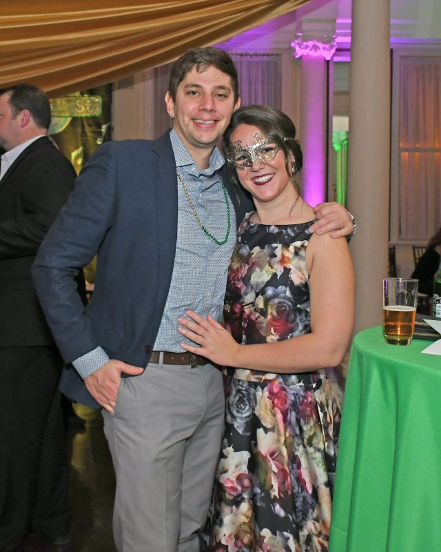 Couple smiling at Mardi Gras event for AIM Services