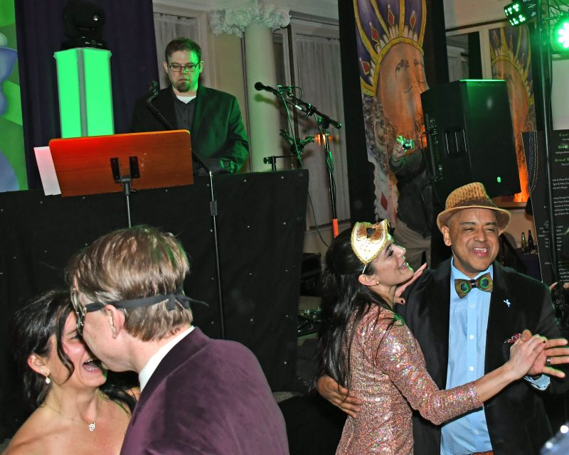 Shot of two couples dancing at Mardi Gras event for AIM Services