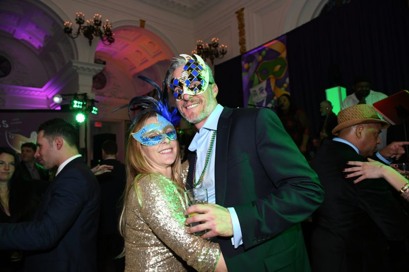 Couple in matching blue and gold masks at Mardi Gras for AIM Services