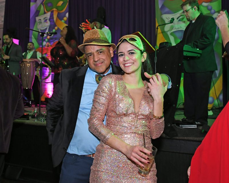 Two people smiling on dance floor at Mardi Gras event for AIM Services