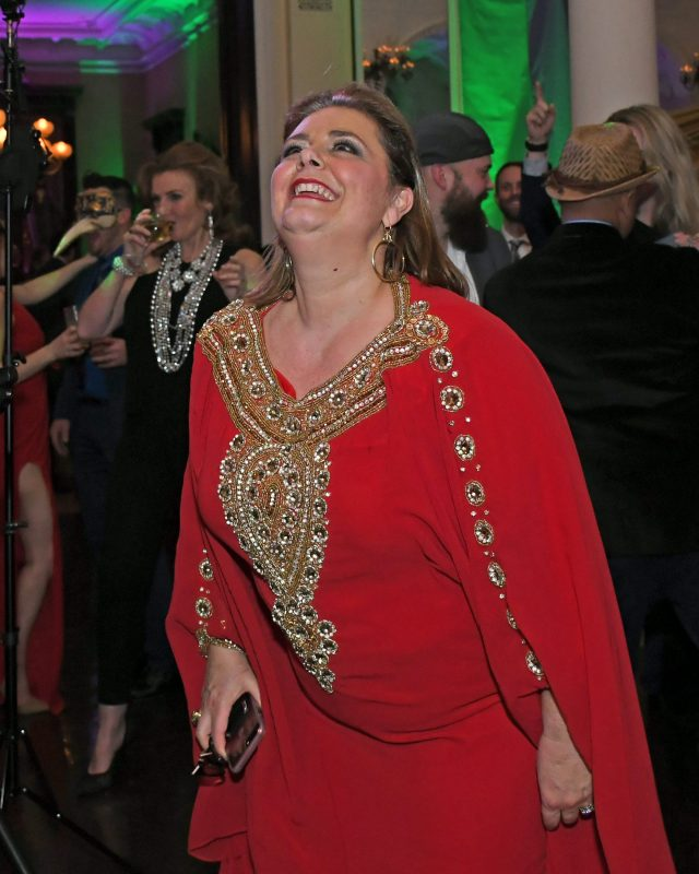 Woman in red dress dancing at Mardi Gras event for AIM Services