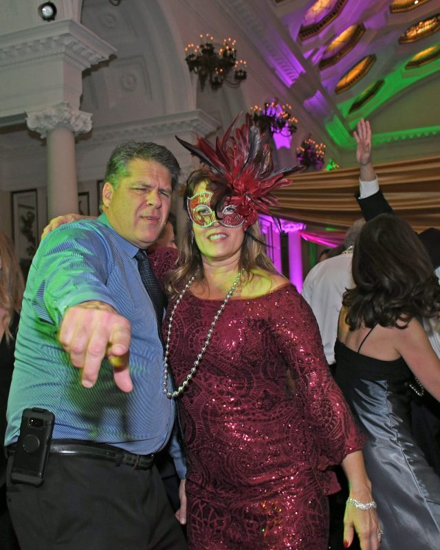 Couple dancing at Mardi Gras event for AIM Services