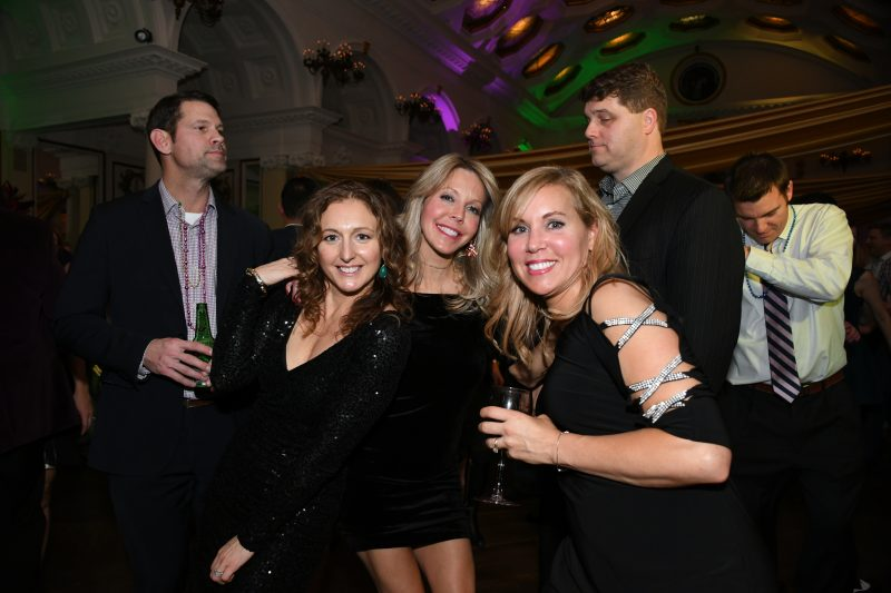 Group of three women smiling on dance floor at Mardi Gras event for AIM Services