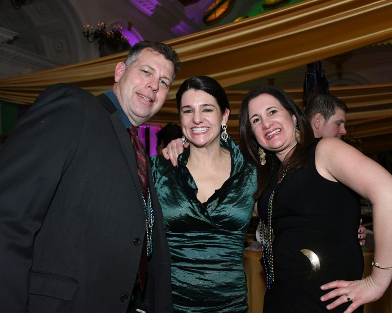 Three people smiling at Mardi Gras event for AIM Services