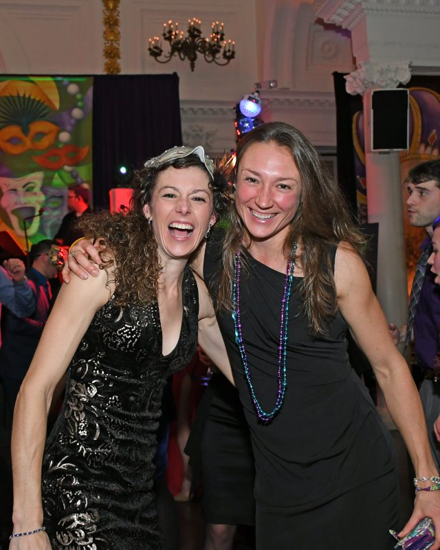 Two women laughing and smiling at Mardi Gras event for AIM Services
