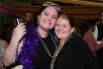 Two women with beads smiling at Mardi Gras event for AIM Services