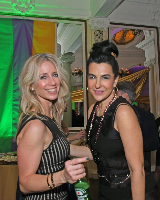 Two women smiling at Mardi Gras event for AIM Services