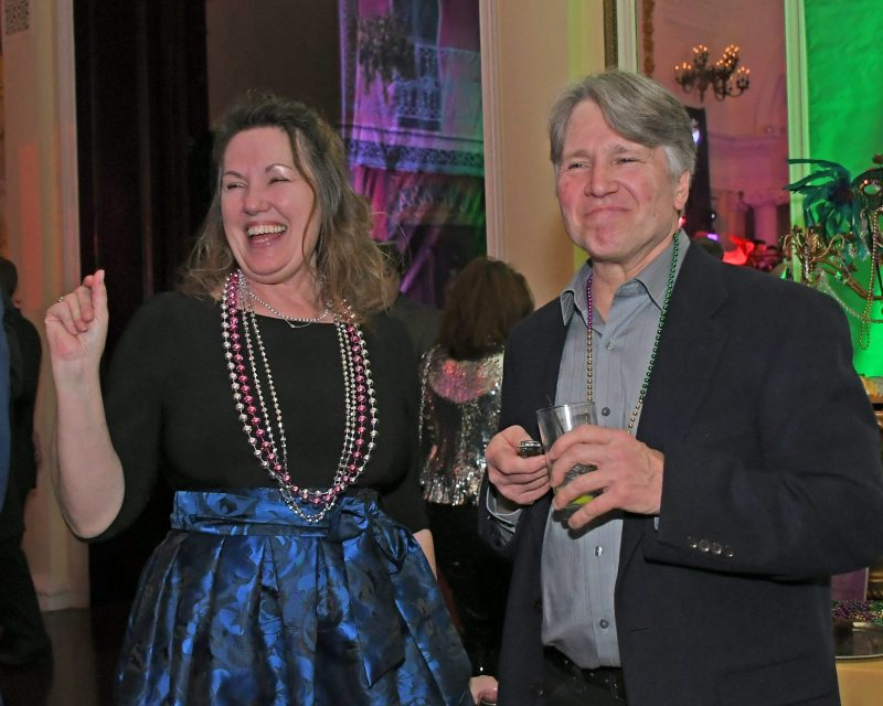 Two people smiling and laughing at AIM Services Mardi Gras event
