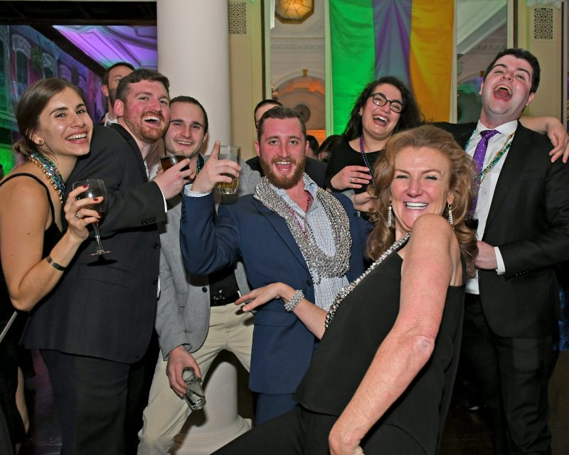 Group of seven people laughing and dancing at Mardi Gras to benefit AIM Services