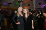 Two women smiling on dance floor at Mardi Gras event for AIM Services