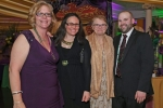 Group of four people at Mardi Gras event for AIM Services