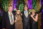 Two couples posing for photo at Mardi Gras event