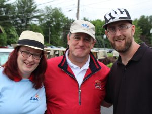 Chris Lyons, Executive Director pictured with two people supported by AIM