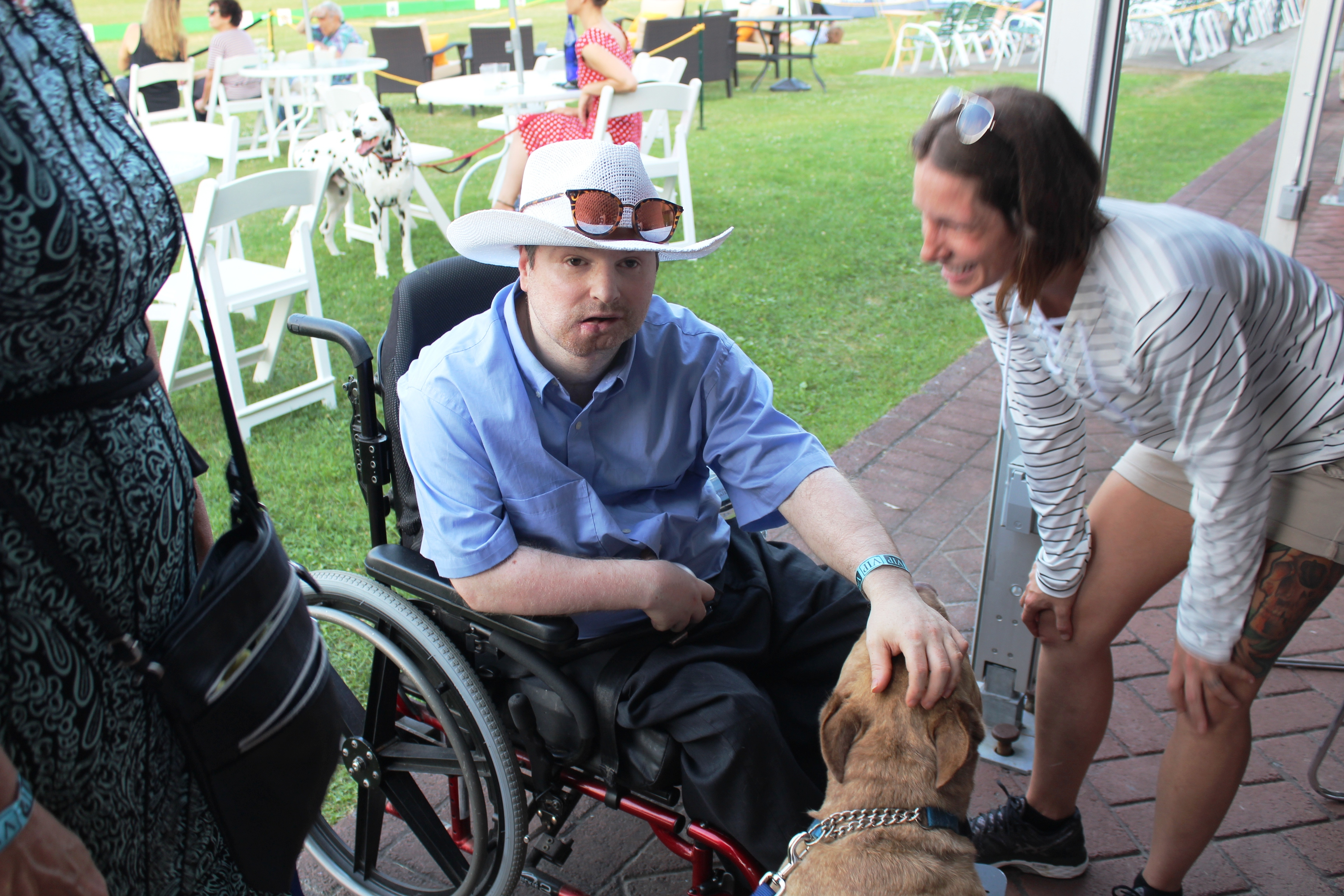 Man in wheelchair petting dog at the Saratoga Dog & Pony Show to benefit AIM Services, Inc.