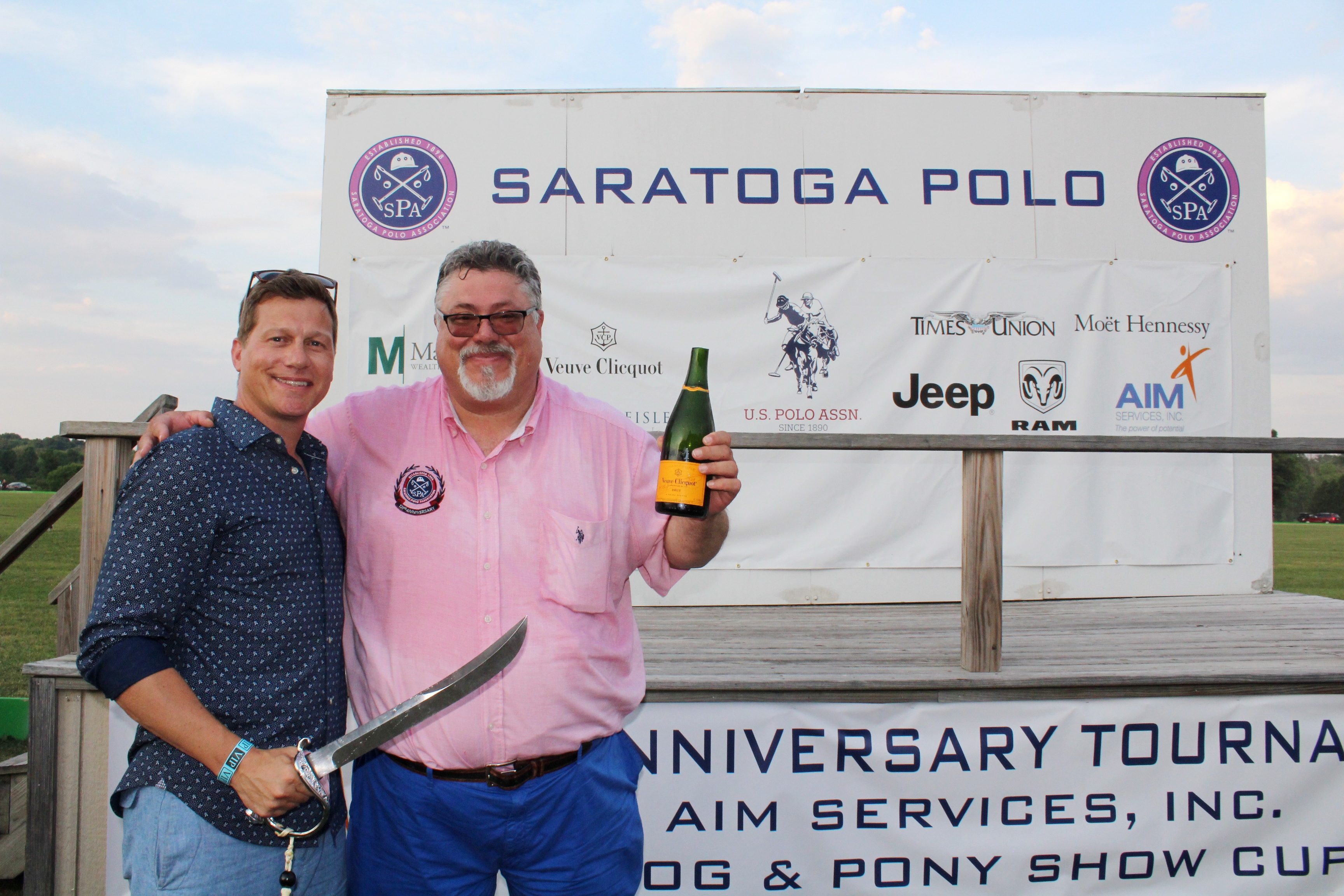 Two men with sabored champagne bottle and sword at the Saratoga Dog & Pony Show to benefit AIM Services, Inc.