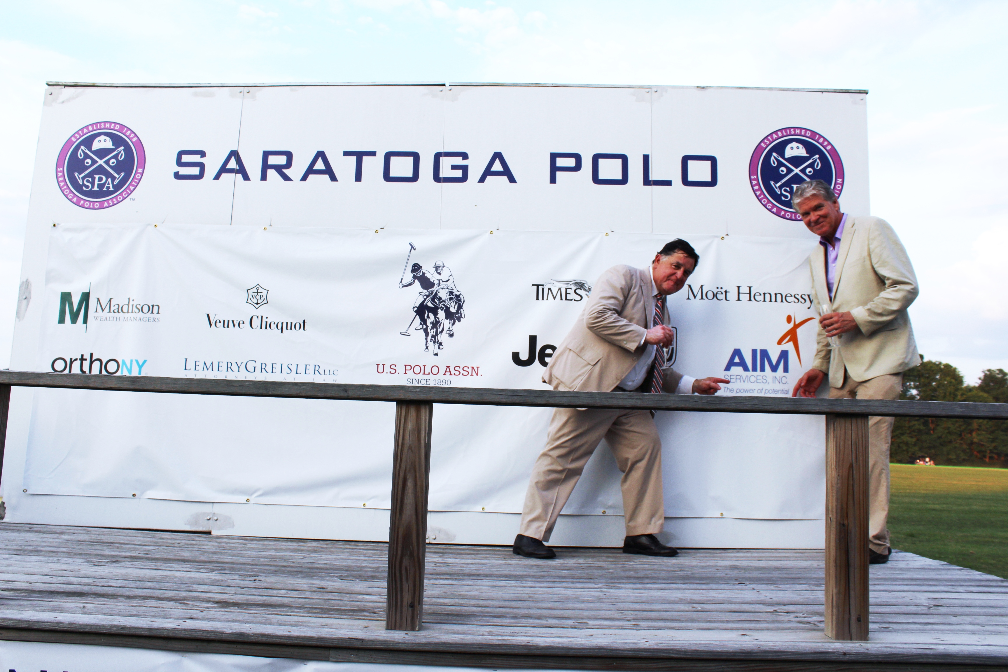 Chris Lyons and Walt Adams pointing at AIM logo at the Saratoga Dog & Pony Show to benefit AIM Services, Inc.