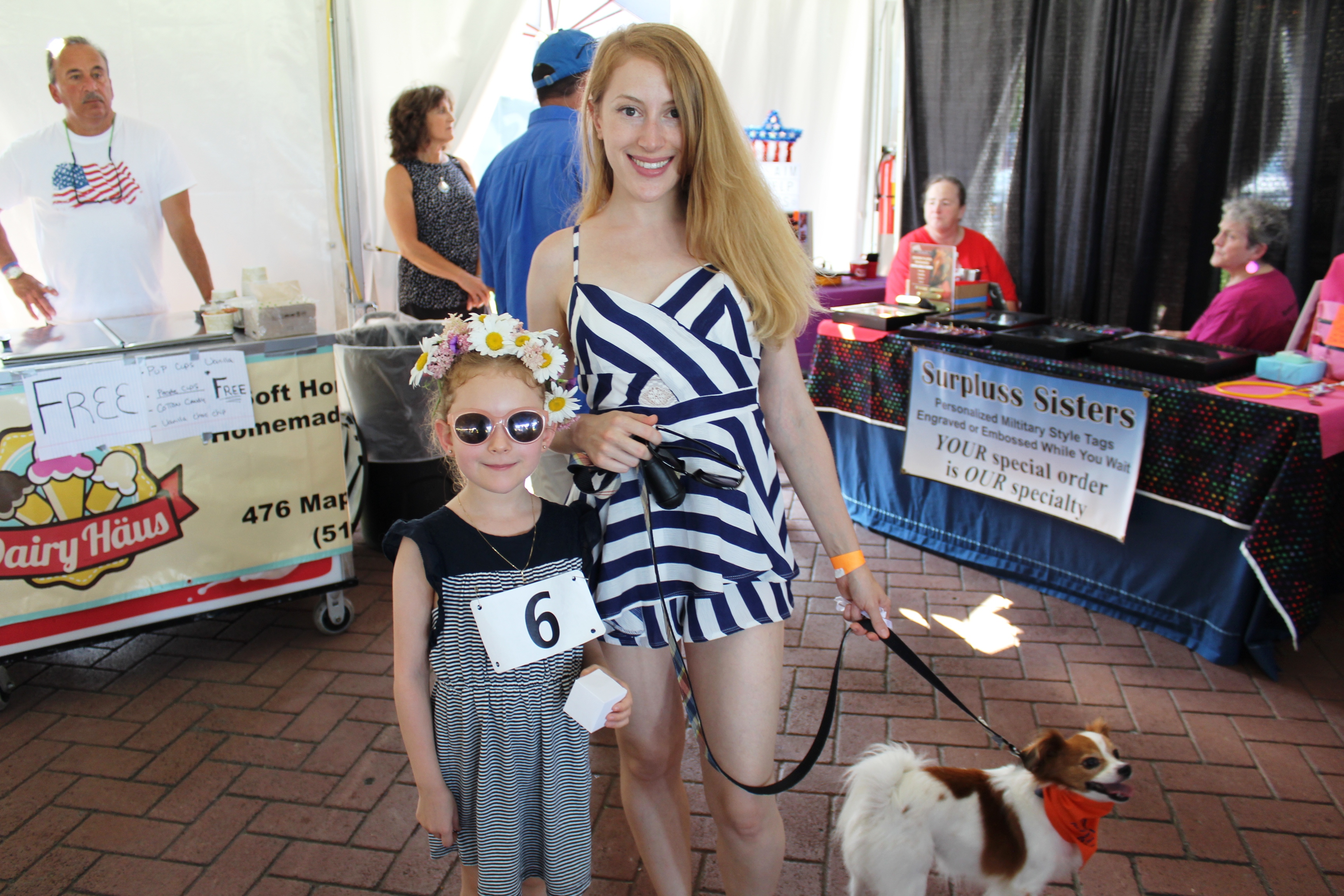 Teen girl with young girl smiling with dog at the Saratoga Dog & Pony Show to benefit AIM Services, Inc.