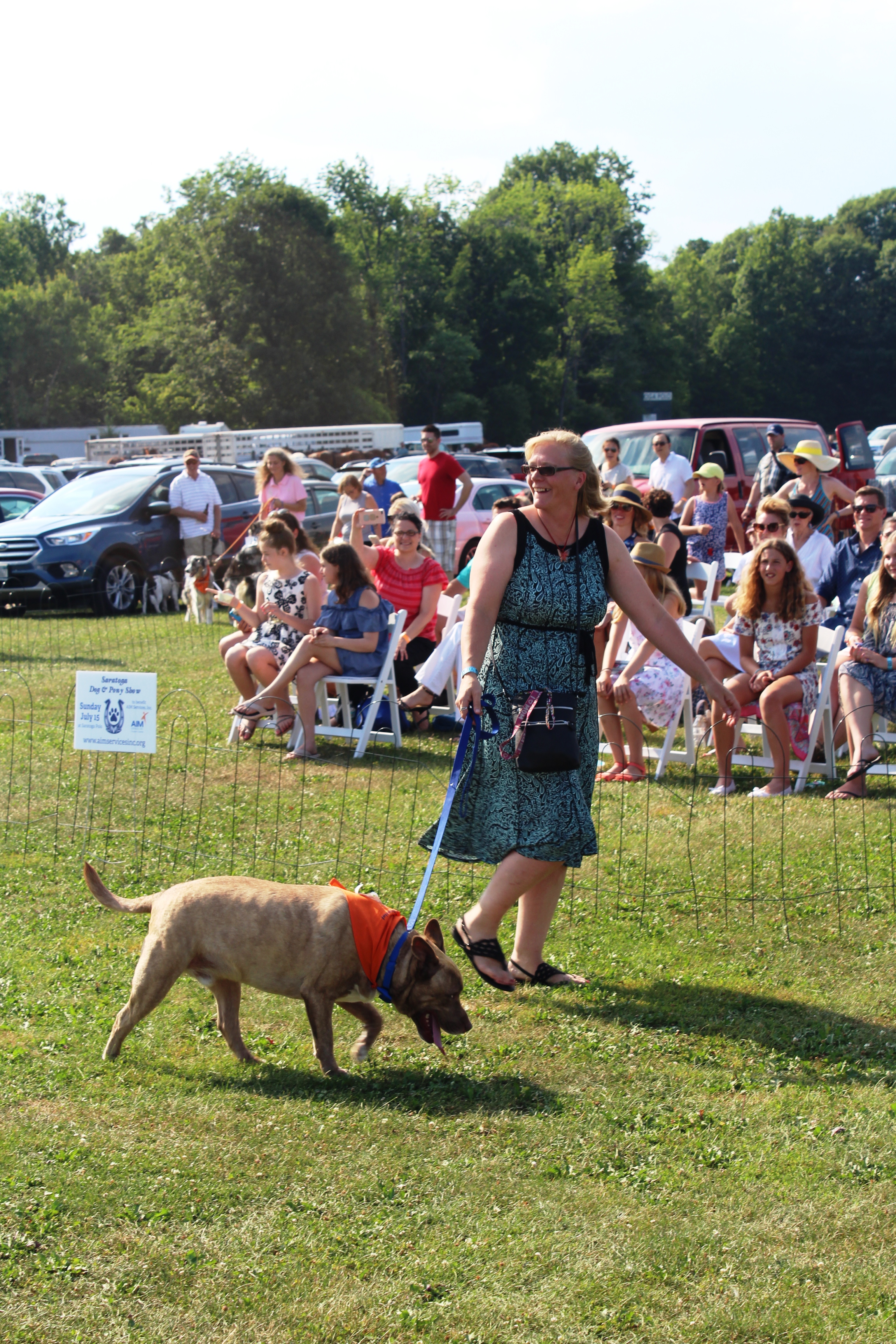 Woman smiling walking dog at the Saratoga Dog's Pony Show to benefit AIM Services, Inc.