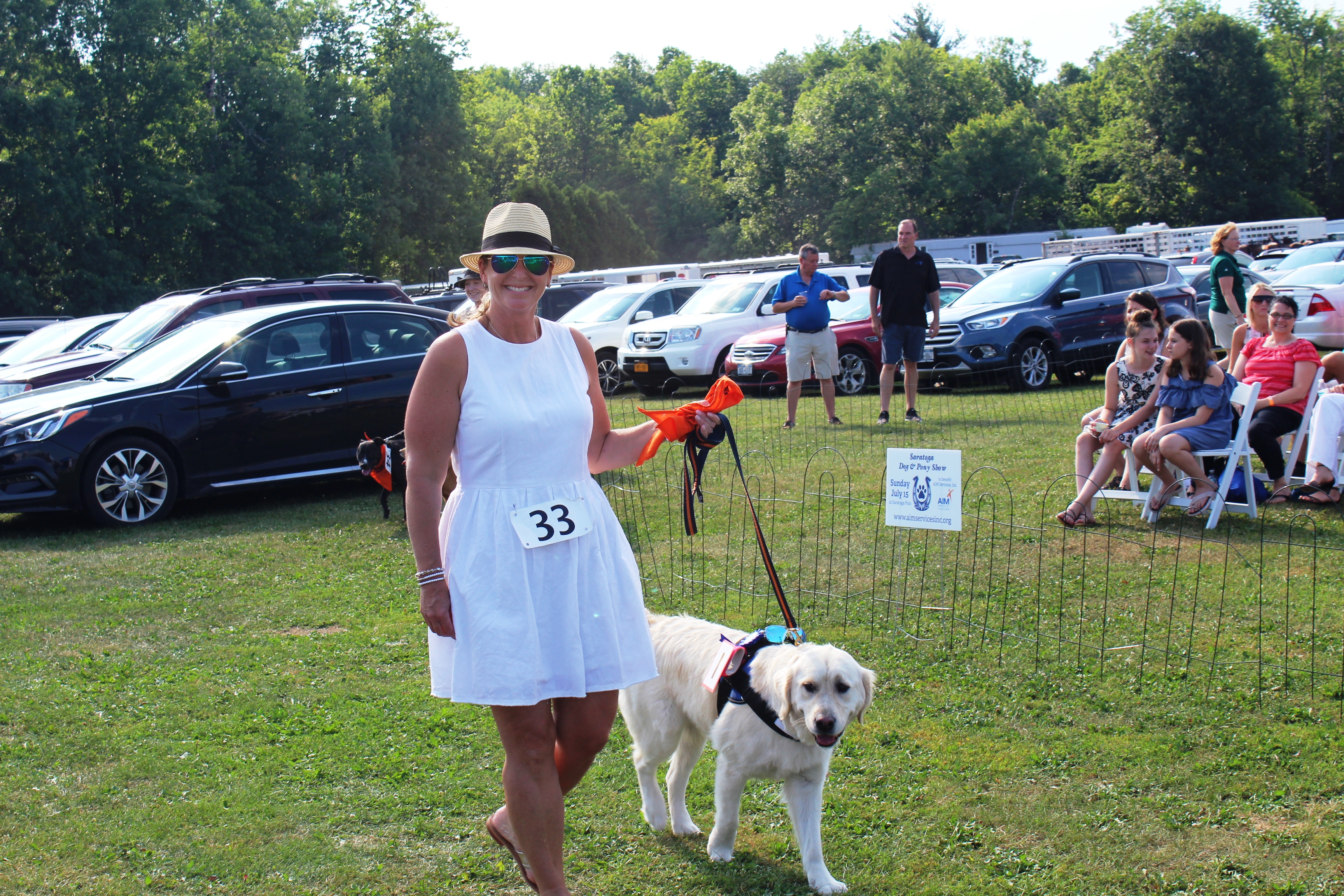 Woman smiling with dog at the Saratoga Dogs Pony Show to benefit AIM Services, Inc.