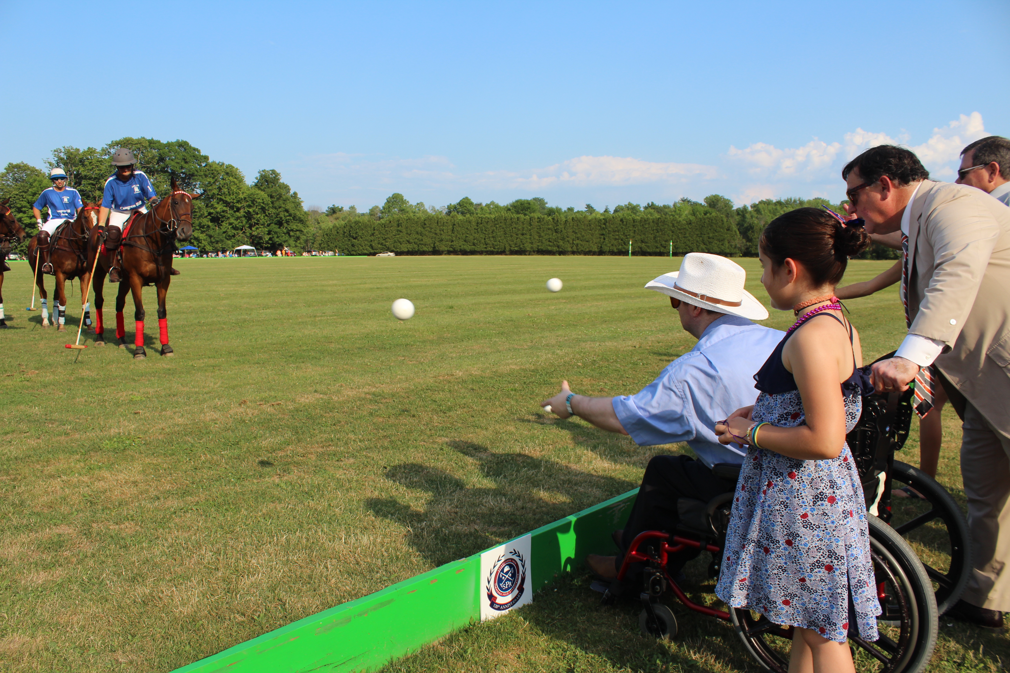 Man in wheelchair throwing first ball for Polo at the Saratoga Dog & Pony Show to benefit AIM Services, Inc.