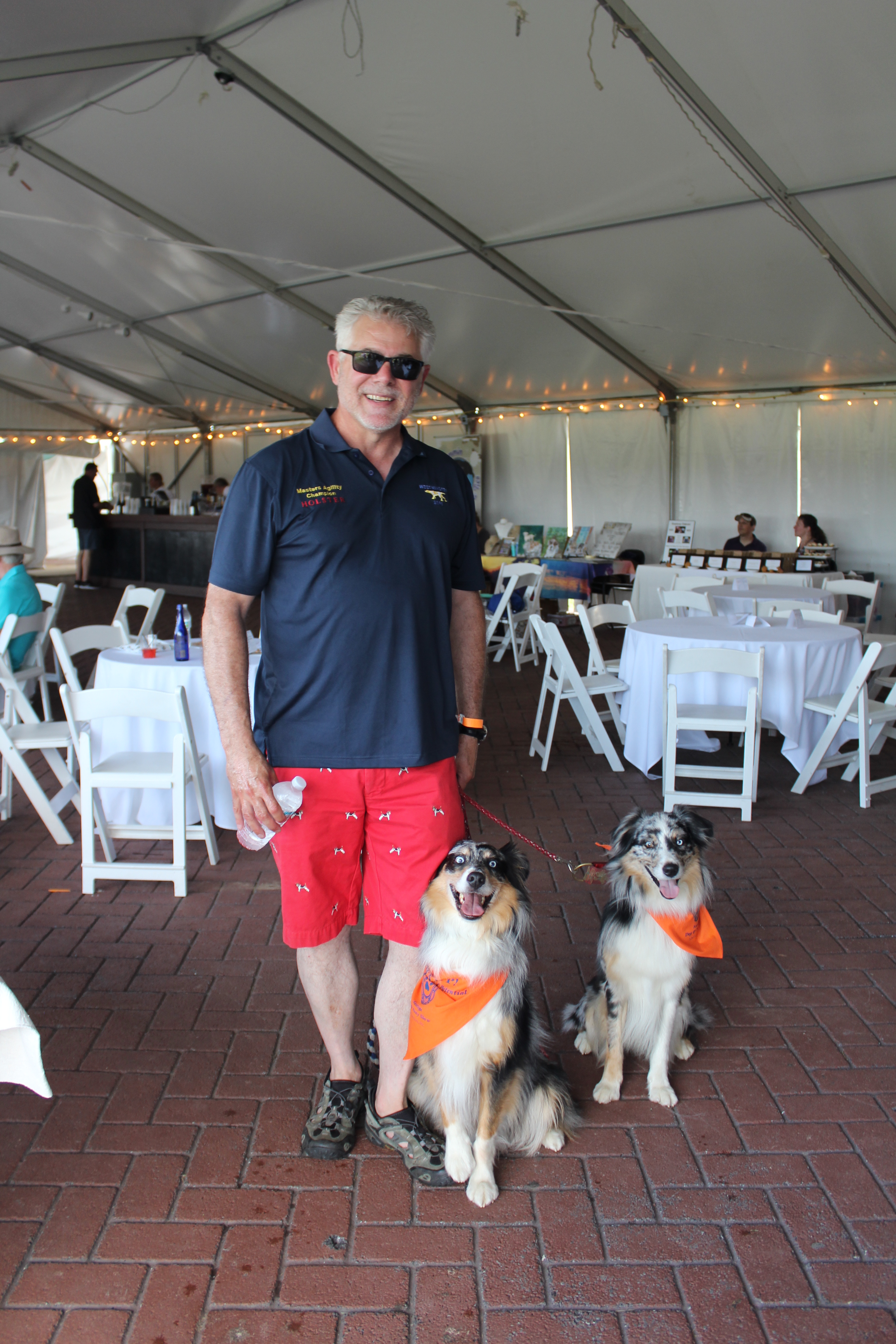 Man smiling with two dogs at the Saratoga Dog & Pony Show to benefit AIM Services, Inc.