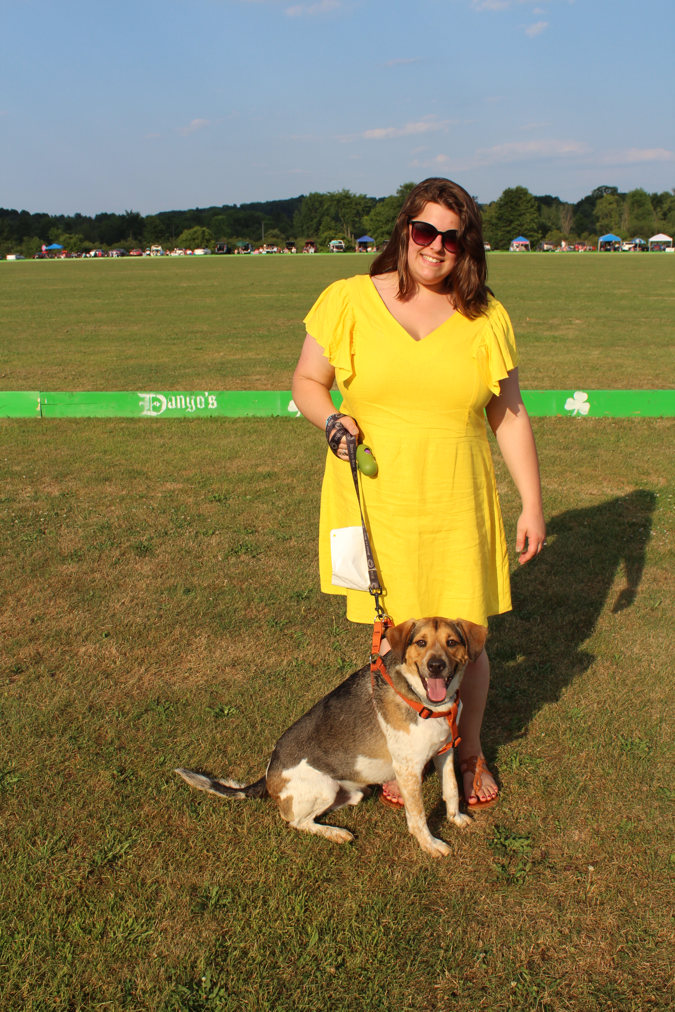 Woman in yellow dress with beagle mix dog at the Saratoga Dog & Pony Show to benefit AIM Services, Inc.