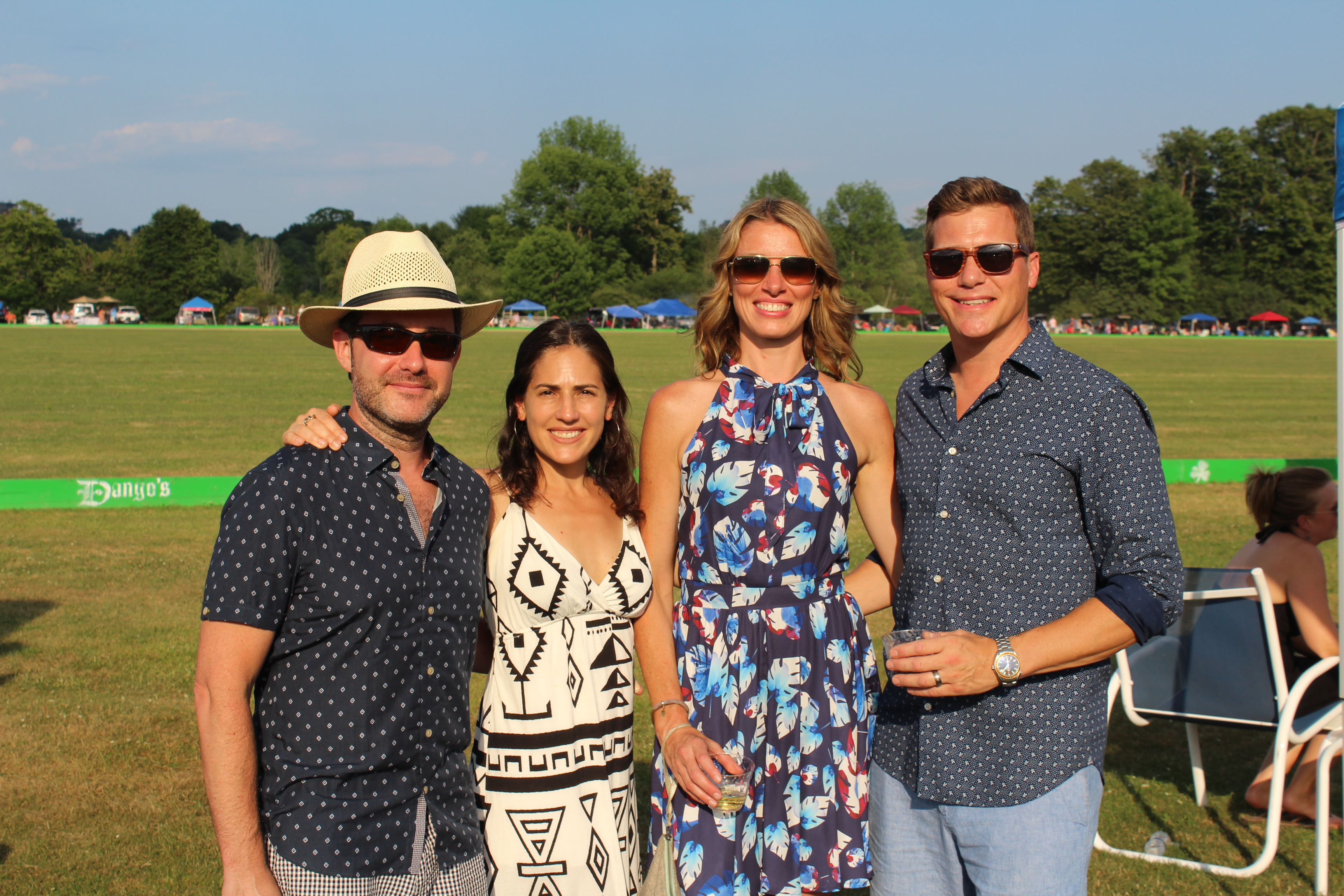 Four people smiling at the Saratoga Dog & Pony Show to benefit AIM Services, Inc.