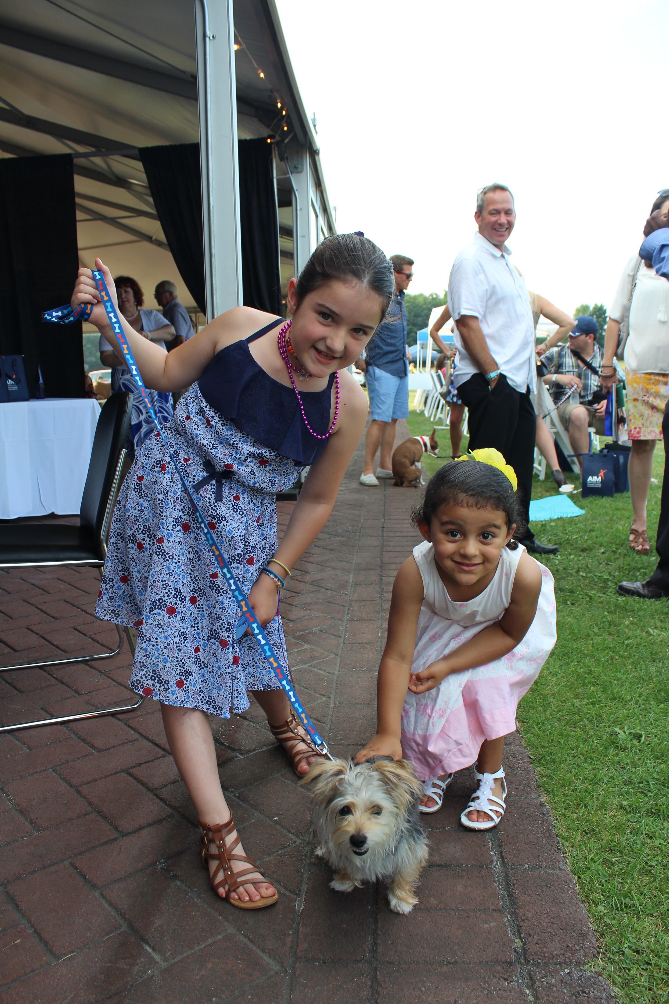 Two young girls smiling with small dog at the Saratoga Dogs Pony Show to benefit AIM Services, Inc.