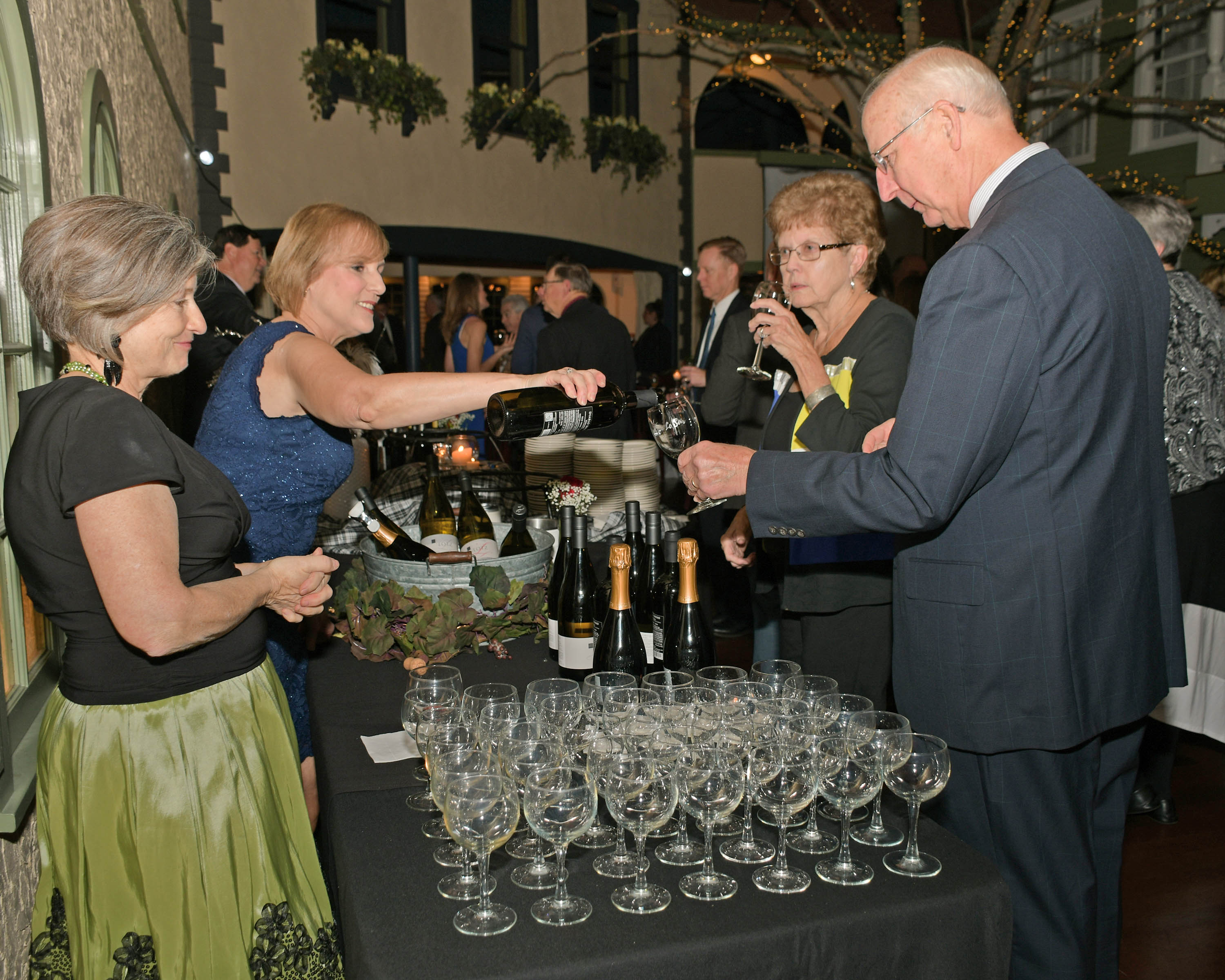 Vin Le Soir to benefit AIM Services, Inc. couple getting wine poured