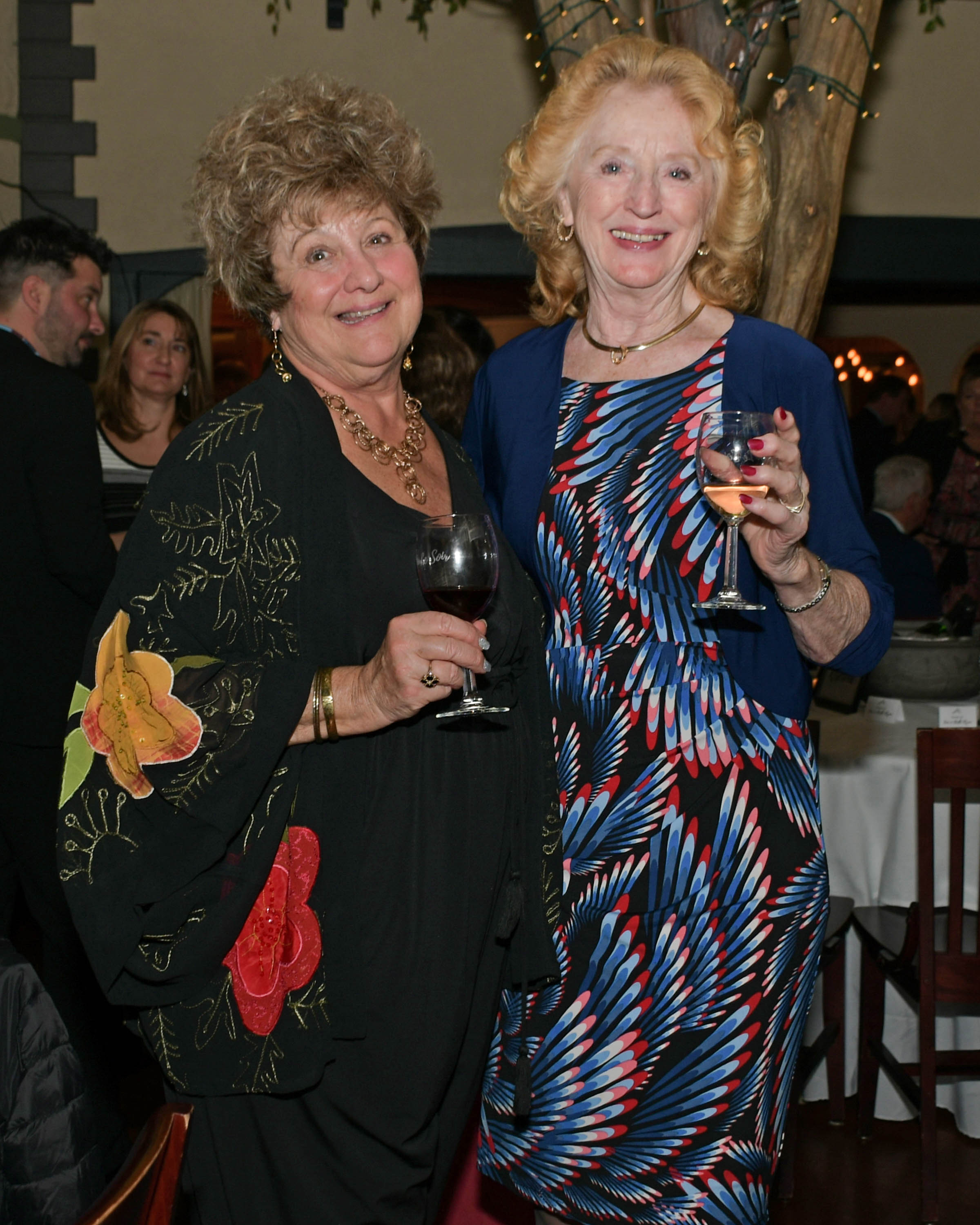 Vin Le Soir to benefit AIM Services, Inc. two women with wine at the event