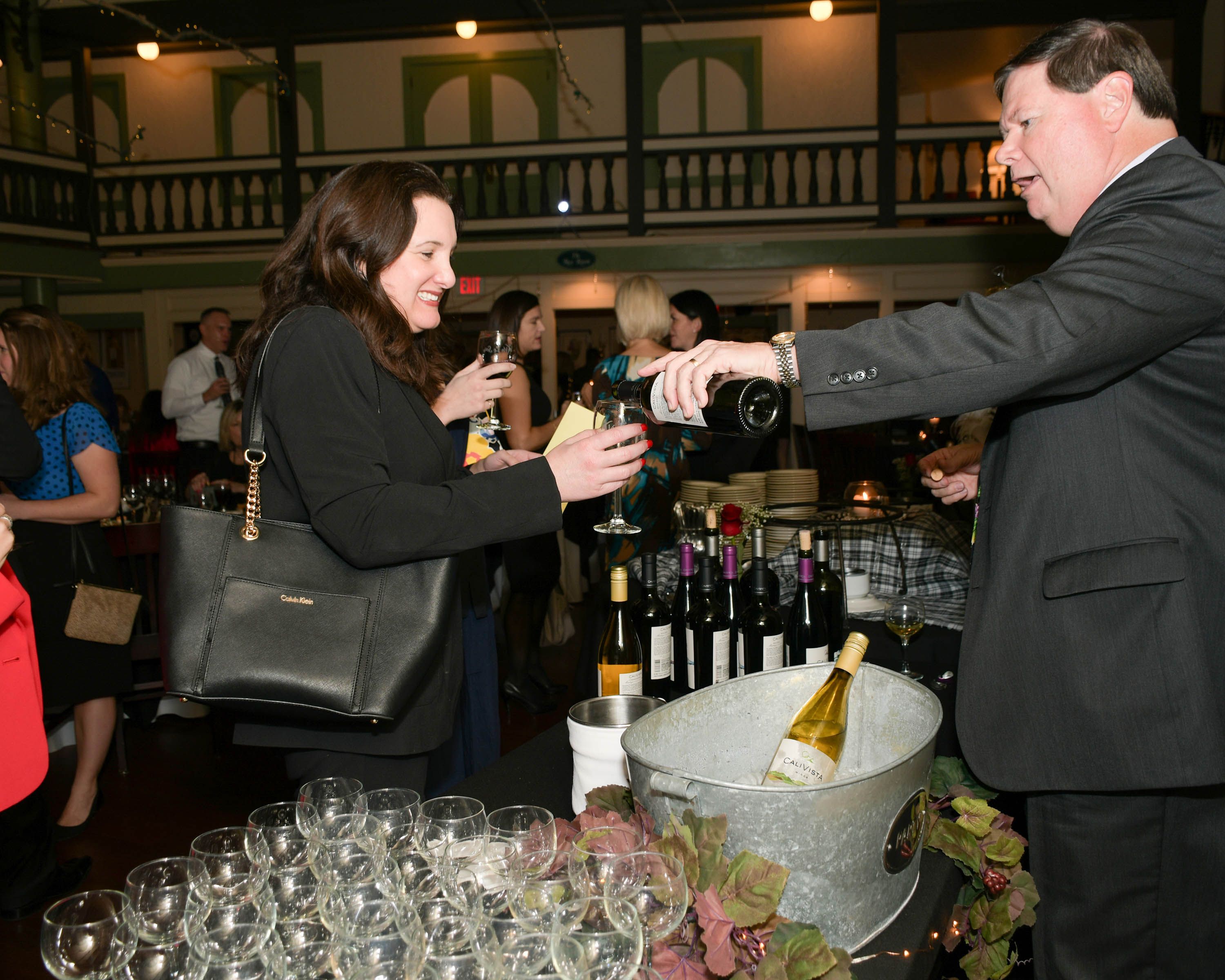 Vin Le Soir to benefit AIM Services, Inc. woman being poured wine from Specialty Wines and More