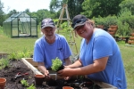 2 People putting plants in garden table - AIM Services, Inc.