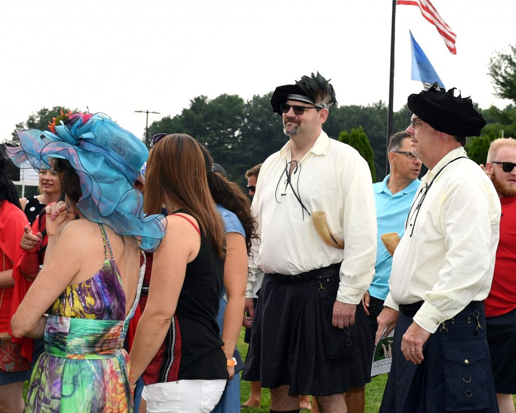 Men dressed in quilts at AIM Services Croquet on the Green event