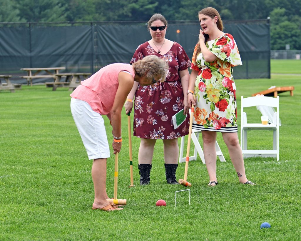 Group of three woman playing croquet at AIM Services Croquet on the Green event