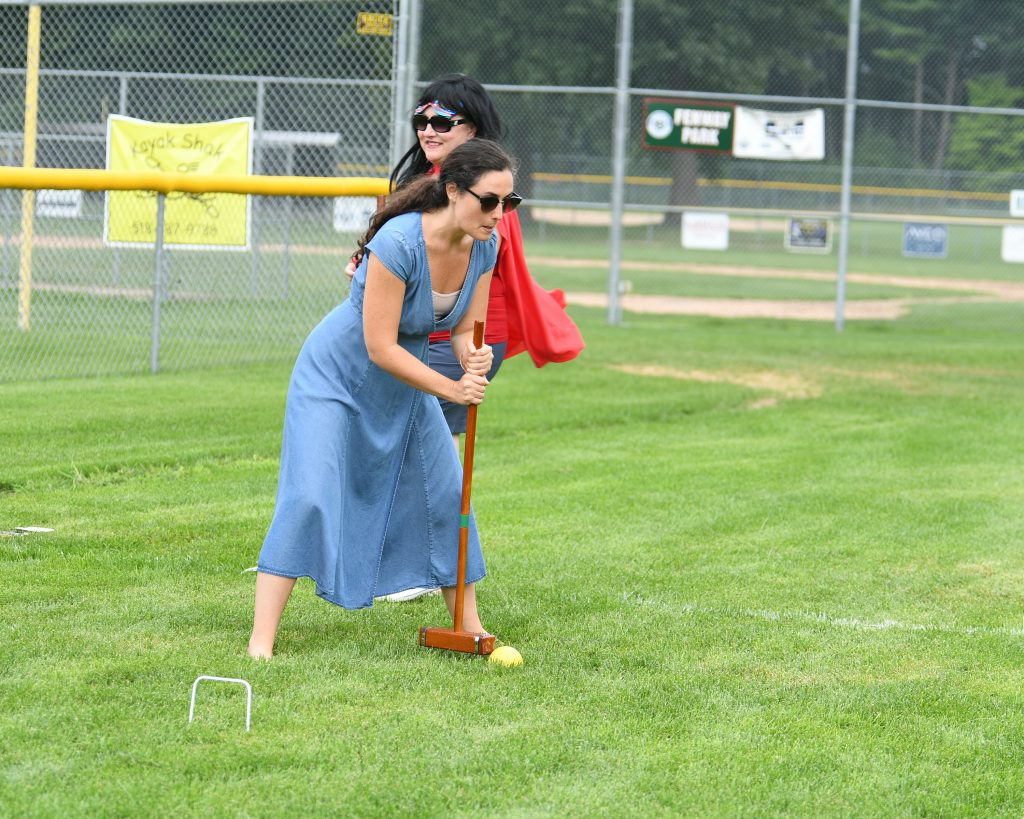 Woman in blue dress lining up her shot at AIM Services Croquet on the Green event
