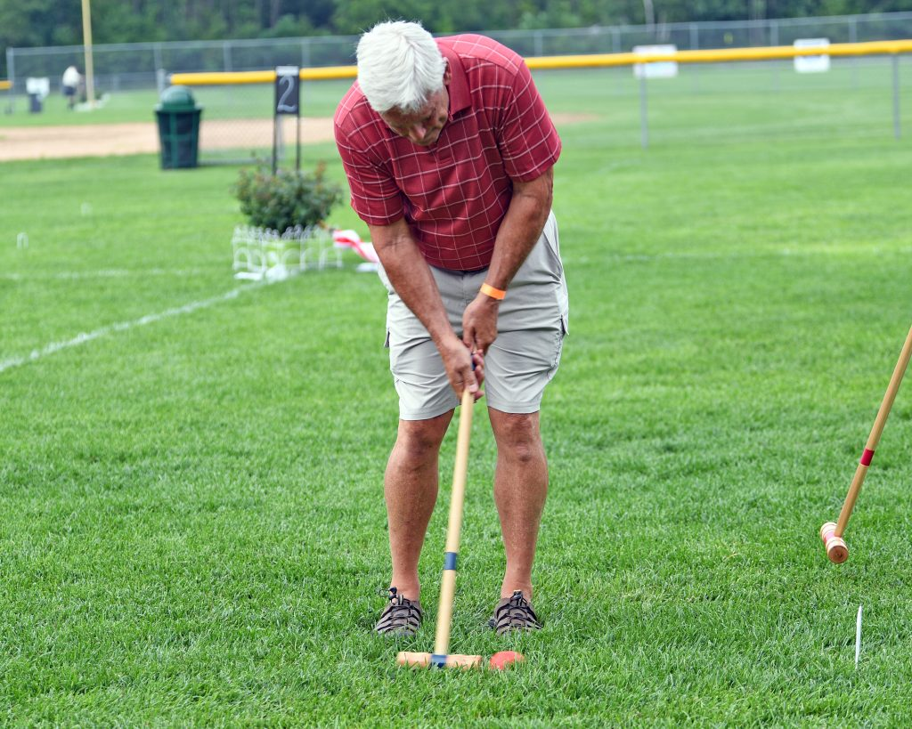 Man taking a shot at AIM Services Croquet on the Green event