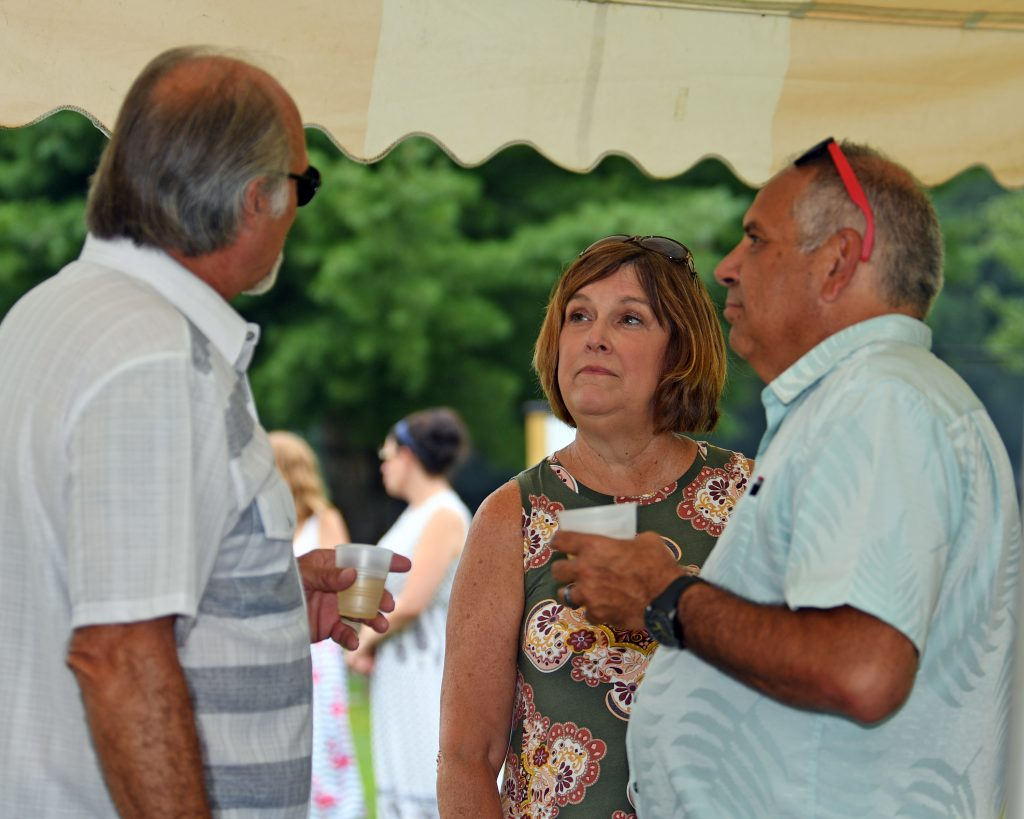 Group of three people talking under a tent with drinks at AIM Services Croquet on the Green event