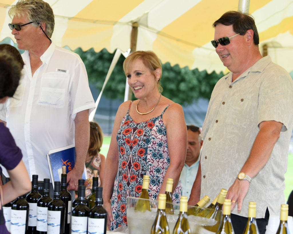 two people smiling over a table of wine bottles at AIM Services Croquet on the Green event