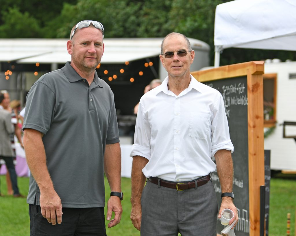 Two men looking at camera at AIM Services Croquet on the Green event