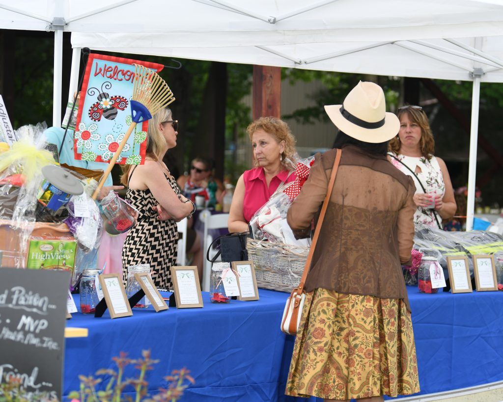 Group of people standing around raffle table at AIM Services Croquet on the Green event