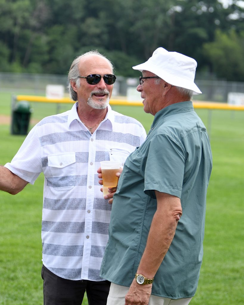Group of two men talking with beer in hand at AIM Services Croquet on the Green event