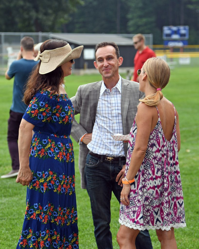 Ramon Dominguez and wife talking with a woman at AIM Services Croquet on the Green event