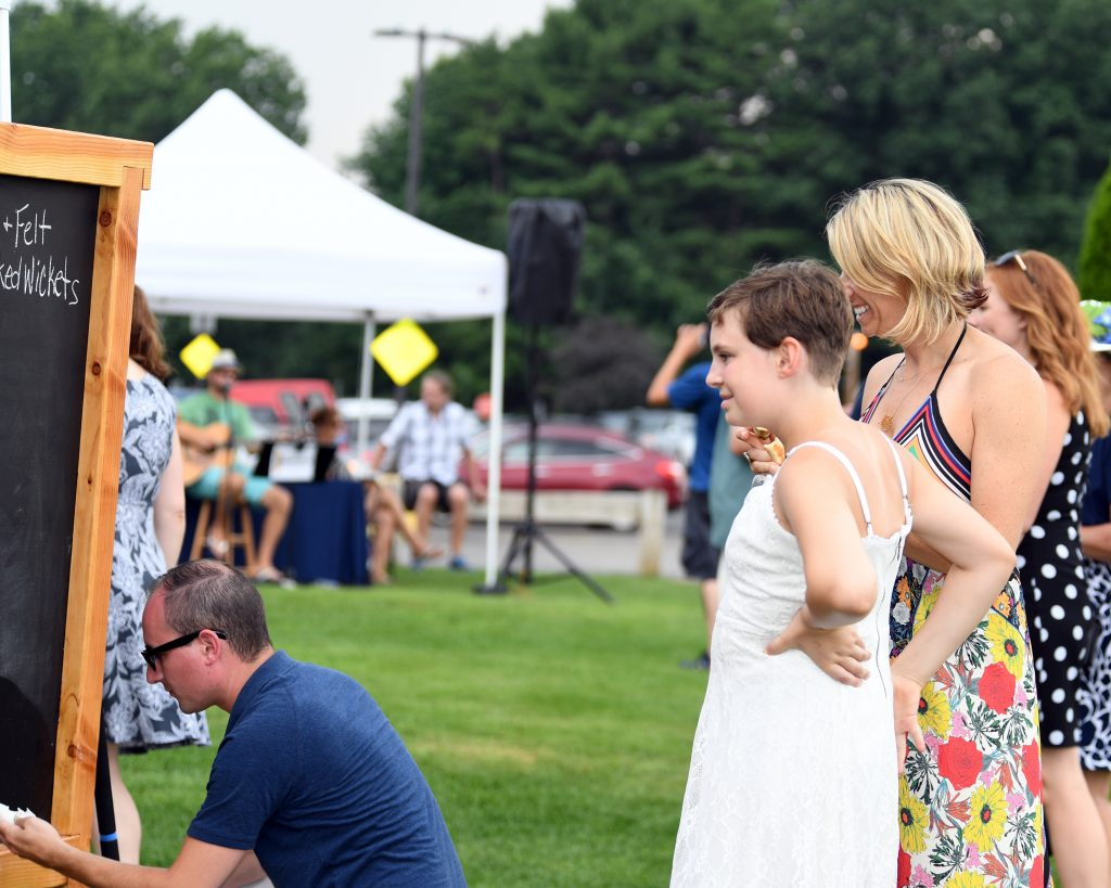Group of people watching the tournament judge write in a chalk board at AIM Services Croquet on the Green event
