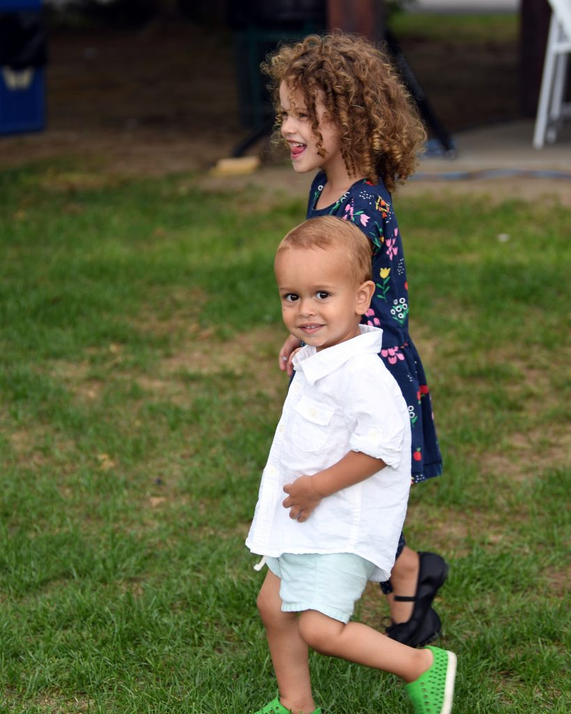Two young children walking holding hands at AIM Services Croquet on the Green event